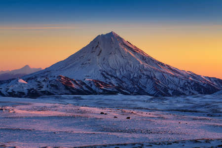 Stunning winter mountain landscape of Kamchatka Peninsula - beautiful morning snow capped cone of volcano at sunrise, full daylight arrives and scenery yellow-blue sky on horizon. Russian Far East.