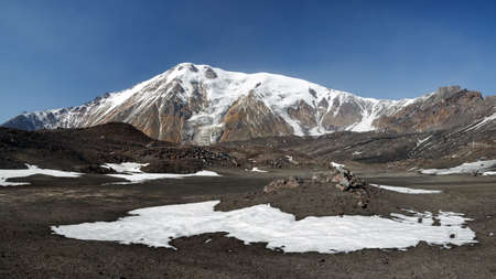 Panorama volcano landscape of Kamchatka Peninsula: beautiful view of cone of Ostry Tolbachik Volcano in Klyuchevskaya Group of Volcanoes on sunny day with clear blue sky. Eurasia, Russian Far East. Stock Photo