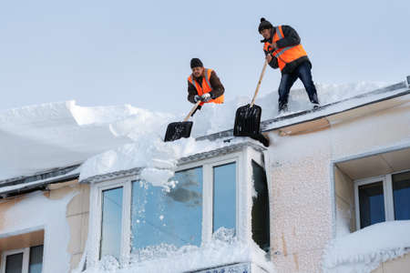 PETROPAVLOVSK CITY, KAMCHATKA PENINSULA, RUSSIA - DEC 27, 2017: Workers with snow shovels carry out winter cleaning of roof of building from snow and ice after heavy snow cyclone (snowstorm, blizzard)