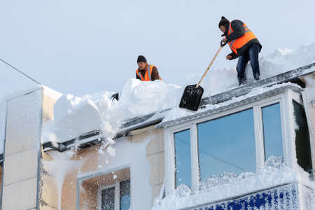 PETROPAVLOVSK CITY, KAMCHATKA PENINSULA, RUSSIA - DEC 27, 2017: Workers in orange vests with snow shovels cleaning snow drifts from roof of multistory building after bad weather (snowstorms, blizzard)