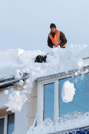 PETROPAVLOVSK KAMCHATSKY CITY, KAMCHATKA, RUSSIA - DEC 27, 2017: Worker with snow shovels carry out cleaning of roof of residential building from snow and ice after heavy winter snow cyclone, blizzard