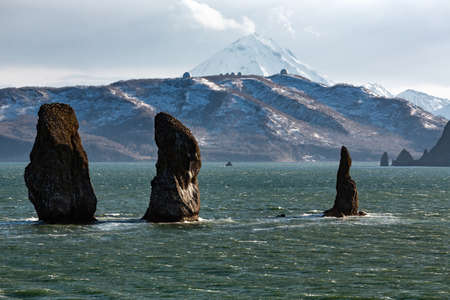 캄차카의 그림 같은 경치 : 풍경 파도가있는 바다의 바위 섬 - 태평양의 Avachinskaya Bay (Avacha Bay)의 3 형제 암석 - 캄차카 반도의 인기있는 여행지.  스톡 콘텐츠