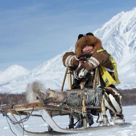 KAMCHATKA, RUSSIA - FEB 25, 2017: Kamchatka musher Roman Mandyatov dressed in national clothes rides on traditional sled of indigenous peoples of Kamchatka. Kamchatka Sled Dog Racing Beringia, Russian 報道画像