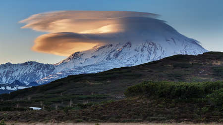 Stunning mountain landscape - lenticular clouds illuminated by sun over picturesque cone of stratovolcano at sunset. Eurasia, Russian Far East, Kamchatka Peninsula, active Mount Ichinsky Volcano. Stock Photo