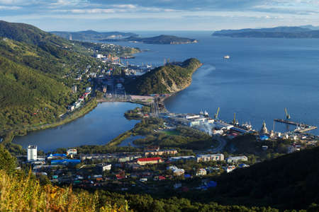 Summer cityscape of Kamchatka Peninsula: top view of center of Petropavlovsk-Kamchatsky City, beautiful mountains along shores of Avacha Bay (Avachinskaya Bay) and Pacific Ocean. Russian Far East. 免版税图像