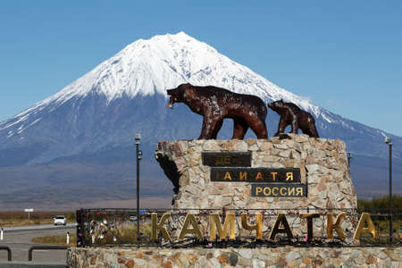 KAMCHATKA PENINSULA, RUSSIAN - SEP 24, 2017: Sculpture of Kamchatka brown bear family. She-bear with teddy bear, inscription on pedestal: Here begins Russia. Kamchatka on background of volcano.