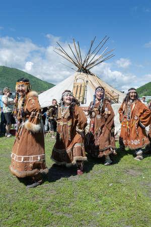 PETROPAVLOVSK CITY, KAMCHATKA PENINSULA, RUSSIA - JULY 11, 2015: Group of women in national clothing aborigine of Kamchatka expression dancing near yaranga. Public concert national folklore dance group on Fishermans Day Editöryel