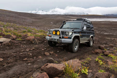 KAMCHATKA PENINSULA, RUSSIA - SEP 17, 2016: Extreme off-road expedition auto Toyota Land Cruiser Prado (70 series) driving on mountain road on background of volcanic landscape in cloudy autumn weather
