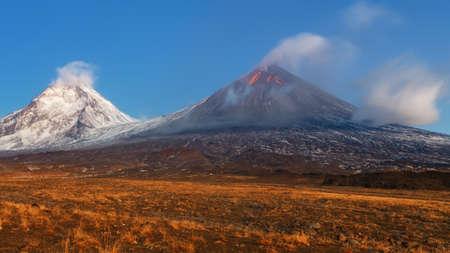Autumn mountain landscape view at sunrise of eruption active Klyuchevskoy Volcano (Klyuchevskaya Sopka) - highest mountain on Kamchatka Peninsula (Russian Far East), highest active volcano of Eurasia. 免版税图像