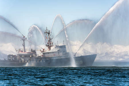 KAMCHATKA, RUSSIA - APR 27, 2019: Rescue and salvage ship of Pacific Fleet of Russia spraying water on sea for supporting emergency case of fire of warships, cargo ships, oil and gas industry. 에디토리얼