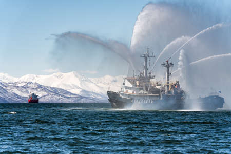 KAMCHATKA, RUSSIA - APR 27, 2019: Firefighting and rescue ship of Pacific Fleet of Russia spraying water on ocean for supporting emergency case of fire of warships, cargo ships, oil and gas industry.