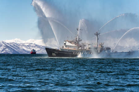 KAMCHATKA PENINSULA, RUSSIA - APR 27, 2019: Fire fighting and rescue ship of Pacific Fleet of Russia spraying water on sea for supporting emergency case of fire of warships, passengers and cargo ships