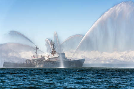 KAMCHATKA, RUSSIA - APR 27, 2019: Firefighting and rescue ship of Pacific Fleet of Russia spraying water on sea for supporting emergency case of fire of warships, passengers, cargo ships, oil tanker.