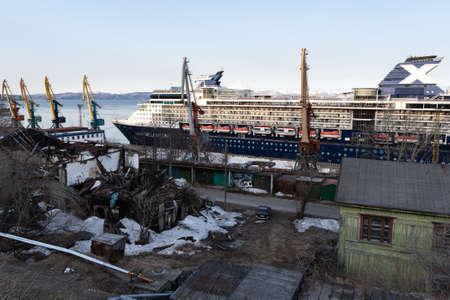 PETROPAVLOVSK CITY, KAMCHATKA PENINSULA, RUSSIA - 2 MAY, 2019: Passenger Cruise Liner Celebrity Millennium anchored at pier in Sea Port Petropavlovsk-Kamchatsky near squalor ruins of building on shore