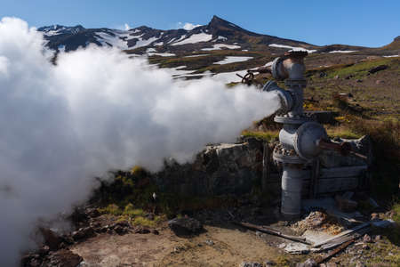 Emission of mineral thermal steam-water mixture from geological well in geothermal deposit area, geothermal power plant on slope of active Mutnovsky Volcano. Russian Far East, Kamchatka Peninsula.