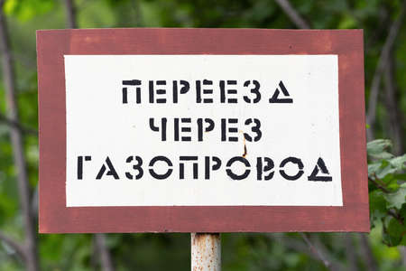 KAMCHATKA PENINSULA, RUSSIA - AUGUST 7, 2019: Warning sign in area of passage of gas main Public Joint Stock Company Gazprom (Gazprom PJSC), inscription in Russian: