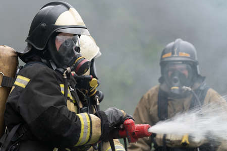"""KAMCHATKA PENINSULA, RUSSIA - AUG 7, 2019: Firefighters of Fire Department â""""– 1 of Federal Fire Service in Kamchatka Territory during fire extinguishing, training to overcome fire zone of psychological training for firefighters. 에디토리얼"""