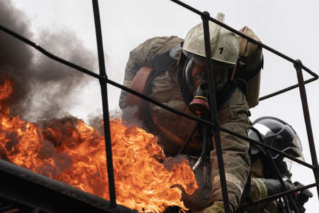 PETROPAVLOVSK-KAMCHATSKY, KAMCHATKA PENINSULA, RUSSIA - AUG 7, 2019: Firefighters of Fire Department № 1 of Federal Fire Service in Kamchatka during fire extinguishing, training to overcome fire zone of psychological training for firefighters. Stock Photo - 128466234