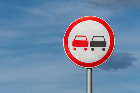 No overtaking road traffic sign with two cars. Information and warning road traffic street sign, compliance with rules. Copy space, background for education, learning and driving courses.