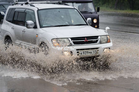 Japanese automobile Mitsubishi Pajero driving flooded street road over deep muddy puddle, splashing drop spray water from wheels. Petropavlovsk-Kamchatsky, Kamchatka Peninsula, Russia - Aug 18, 2018