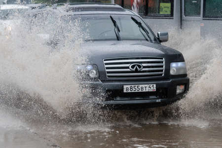 Japanese automobile Infiniti driving on flooded city street road over deep muddy puddle, splashing drop of spray water from wheels. Petropavlovsk-Kamchatsky, Kamchatka Peninsula, Russia - Aug 18, 2018 Redakční
