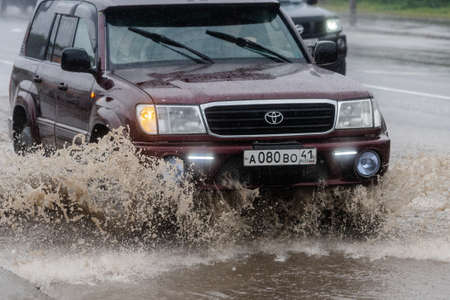 Japanese car Toyota Land Cruiser driving on flooded city street road over deep muddy puddle, splashing drop of spray water from wheels. Petropavlovsk-Kamchatsky City, Kamchatka, Russia - Aug 18, 2018