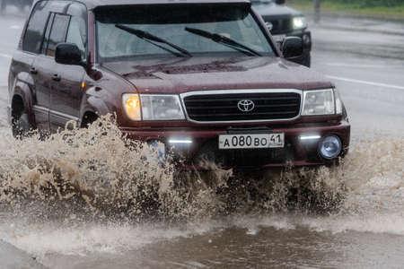 Japanse auto Toyota Land Cruiser rijdt op overstroomde straat in de stad over diepe modderige plas, spattende druppel sproeiwater van wielen. Petropavlovsk-Kamchatsky City, Kamtsjatka, Rusland - 18 aug. 2018