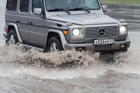 Automobile Mercedes-Benz G-Wagen driving on flooded street road over deep muddy puddle, splashing drop of spray water from wheels. Petropavlovsk-Kamchatsky, Kamchatka Peninsula, Russia - Aug 18, 2018 Redakční