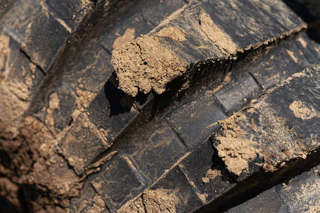 Close-up view of old used rubber mud terrain tire with worn wear-resistant tread. Black muddy off-road tire on 4x4 truck with adhering dirt after overcoming an impassable off road trip in mountains.