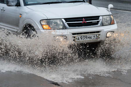 Close-up view of japanese SUV Mitsubishi Pajero driving on flooded street road over deep muddy puddle, splashing drop of spray water from wheels during rainy weather. Kamchatka, Russia - Aug 18, 2018 Redakční