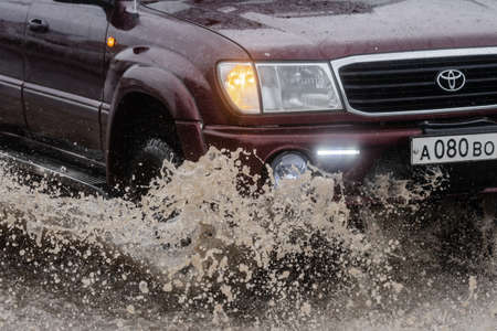 Close-up view of Japanese car Toyota Land Cruiser driving on flooded road over deep muddy puddle and splashing drop of spray water from wheels during rainy weather. Kamchatka, Russia - Aug 18, 2018