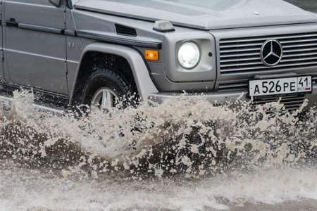 Close-up view of Mercedes-Benz G-Class, G-Wagen driving on flooded road over deep muddy puddle and splashing drop of spray water from wheels during rainy weather. Kamchatka, Russia - August 18, 2018 Redakční