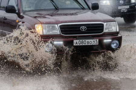 Japanese car Toyota Land Cruiser driving on flooded street road over deep muddy puddle and splashing drop of spray water from wheels. Petropavlovsk City, Kamchatka Peninsula, Russia - August 18, 2018 Redakční