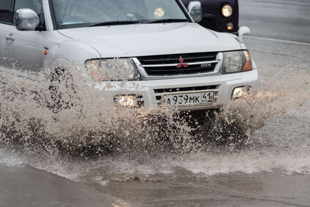 Japanese SUV Mitsubishi Pajero driving on flooded town street road over deep muddy puddle, splashing drop of spray water from wheels. Petropavlovsk City, Kamchatka Peninsula, Russia - August 18, 2018