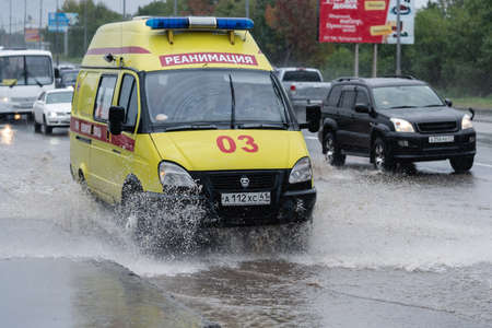 State Emergency Ambulance Reanimation Medical van vehicle yellow color driving on city street road over deep muddy puddle, splashing water from wheels. Petropavlovsk, Kamchatka, Russia - Aug 18, 2018.