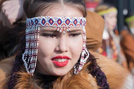 Portrait pretty smiling female in traditional clothing indigenous inhabitants of Kamchatka. Celebration Koryak national ritual holiday Hololo Day of Seal. Kamchatka Region, Russia - Nov 4, 2018