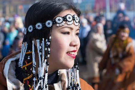 Portrait smiling young woman in traditional clothing indigenous inhabitants of Kamchatka. Celebration Koryak national ritual holiday Hololo Day of Seal. Kamchatka Territory, Russia - November 4, 2018 에디토리얼