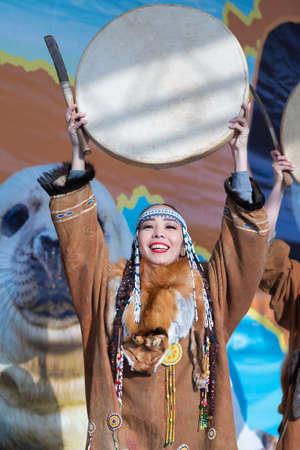 Female dancing with tambourine in national clothing indigenous inhabitants Kamchatka. Concert, celebration Koryak national ritual holiday Hololo Day of Seal. Kamchatka Peninsula, Russia - Nov 4, 2018 에디토리얼