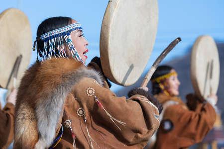 Female dancing with tambourine in national clothing indigenous inhabitants Kamchatka. Concert, celebration Koryak national ritual holiday Day of Seal Hololo. Kamchatka Peninsula, Russia - Nov 4, 2018