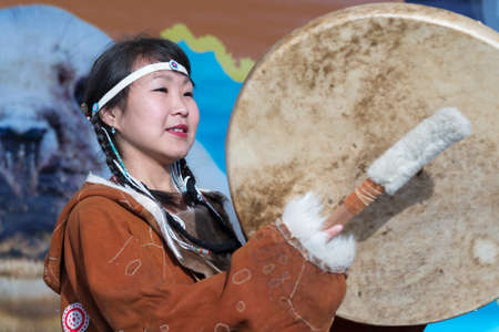 Woman dancing with tambourine in tradition clothing aborigine people Kamchatka. Concert, celebration Koryak national holiday Hololo Day of Seal. Kamchatka Region, Russia - November 4, 2018
