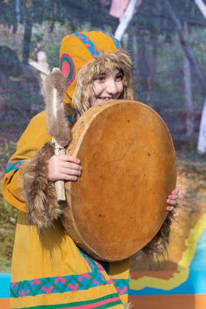Female child dancing with tambourine in national clothing indigenous inhabitants Kamchatka. Concert, celebration Koryak national holiday Hololo - Day of Seal. Kamchatka Peninsula, Russia - Nov 4, 2018