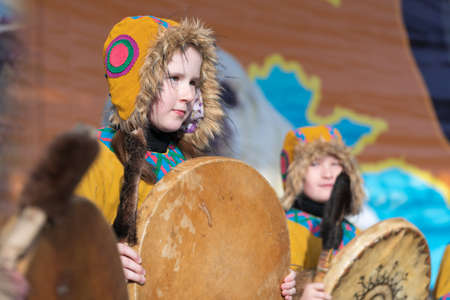 Female child dancing with tambourine in national clothing indigenous inhabitants Kamchatka. Concert, celebration Koryak national holiday Day of Seal - Hololo. Kamchatka Peninsula, Russia - Nov 4, 2018