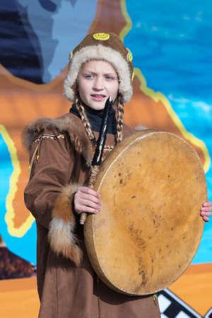 Girl dancing with tambourine in tradition clothing aboriginal people Kamchatka Peninsula. Concert, celebration Koryak national ritual holiday Hololo - Day of Seal. Kamchatka, Russia - Nov 4, 2018 에디토리얼