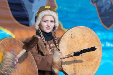 Girl dancing with tambourine in tradition clothing aborigine people Kamchatka Peninsula. Concert, celebration Koryak national ritual holiday Day of Seal - Hololo. Kamchatka, Russia - Nov 4, 2018 에디토리얼
