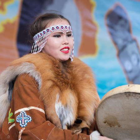 Girl dancing with tambourine in tradition clothing aborigine people Kamchatka Peninsula. Concert, celebration Koryak national ritual holiday Day of Seal - Hololo. Kamchatka, Russia - November 4, 2018 에디토리얼