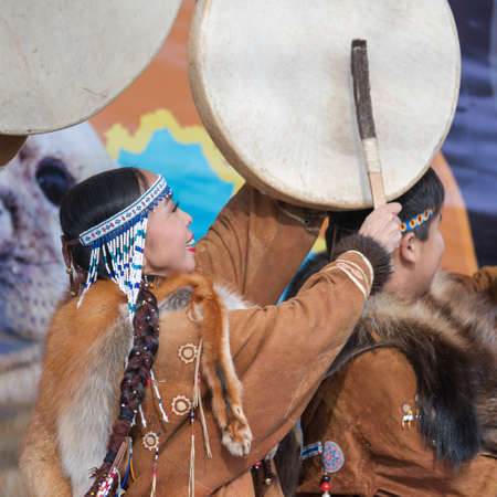 Female dancing with tambourine in tradition clothing indigenous inhabitants Kamchatka. Concert celebration Koryak national holiday Day of Seal - Hololo. Kamchatka, Russian Far East - November 4, 2018