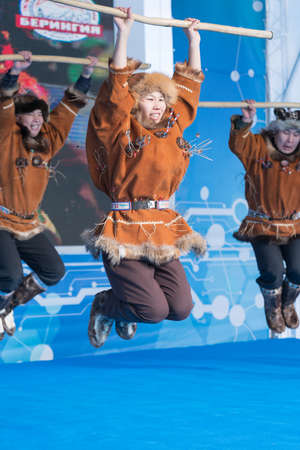 Aborigine female dancer jumping in national clothes of indigenous people Kamchatka. Concert of Kamchatka State Academic Koryak National Dance Ensemble Mengo. Kamchatka Peninsula, Russia - Feb 21, 2019 에디토리얼