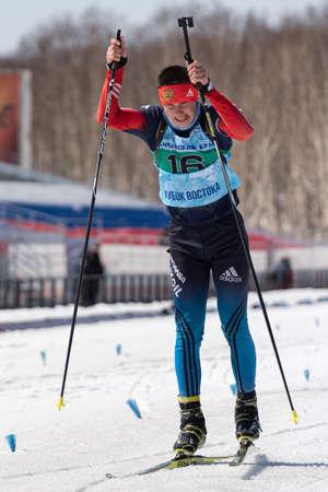 Russian sportsman biathlete Kapustin Aleksandr skiing on ski track distance biathlon arena. Junior biathlon competitions East of Cup. Petropavlovsk City, Kamchatka Peninsula, Russia - April 14, 2019