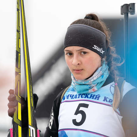 Sportswoman biathlete Knyazeva Elizaveta with skis in hands and rifle behind her after skiing and rifle shooting. Open regional junior biathlon competitions East Cup. Kamchatka, Russia - Apr 12, 2019 에디토리얼