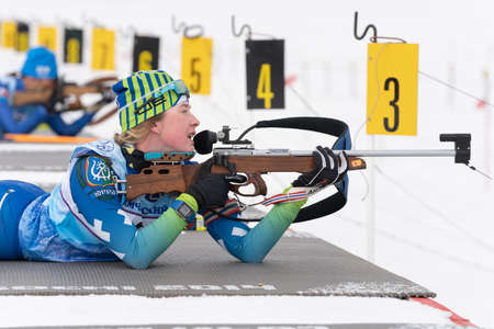 Sportswoman biathlete Legostaeva Anastasia rifle shooting in prone position. Biathlete in shooting range. Regional junior biathlon competitions East of Cup. Kamchatka, Russian Far East - Apr 12, 2019